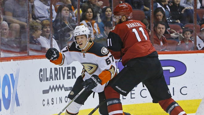 Anaheim Ducks center Rickard Rakell (67) gets checked by Arizona Coyotes center Martin Hanzal (11) during the second period of their NHL game Monday, Feb. 20, 2017 in Glendale, Ariz.