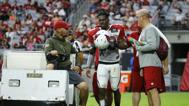 Arizona Cardinals players and staff check on cornerback Ronald Zamort (29) after he was shaken up during their Red & White practice Saturday, July 29, 2017 in Glendale,  Ariz.