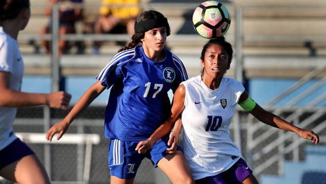 La Vergne's Annette Mateos (17) and Smyrna's  Ashley Barrientos (10) both work their way to the ball during a soccer match on Tuesday, Aug. 28, 2018, in La Vergne.