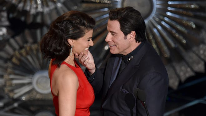 John Travolta, right, touches the face of Idina Menzel as they present the award for best original song at the Oscars at the Dolby Theatre in Los Angeles on Feb. 22, 2015.