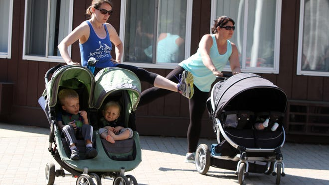 Lisa Waterman of Howell holds a stroller carrying her children, Brayden, 2, and Dylan, 9-months; and Sandy Barndt of Howell holds a stroller carrying her 3-month-old daughter, Evelyn, as they stretch with the Jersey Strong Moms, a mothers with strollers workout group, at Michael J. Tighe Park in Freehold Township.