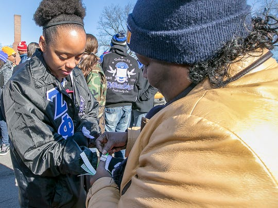 Sha'ron Mallard has a wrist band attached by Diane Leslie as MLK marchers sign up before the event in downtown Murfreesboro Monday.
