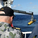 "Commander James Lybrand, Mission Commander ADV Ocean Shield, left, and Chris ""Sharkie"" Moore, Phoenix team leader, watch the launching of the Phoenix International Autonomous Underwater Vehicle (AUV) Artemis as it is craned over the side of Australian Defense Vessel Ocean Shield before launching it in to the southern Indian Ocean in the search of the missing Malaysia Airlines Flight 370 on April 17, 2014."