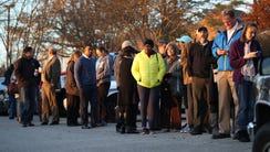 Voters wait in line to cast their ballot at a polling