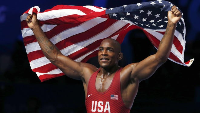 Former Missouri standout J'den Cox of the United States holds a national flag as he celebrates his victory over Alireza Mohammad Karimimachiani of Iran in their gold match during the Wrestling World Championships on Sept. 21 in Nur-Sultan, Kazakhstan.