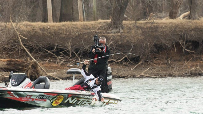 Professional angler Edwin Evers pulls a bass from a lake while being filmed for a Bassmaster TV show.