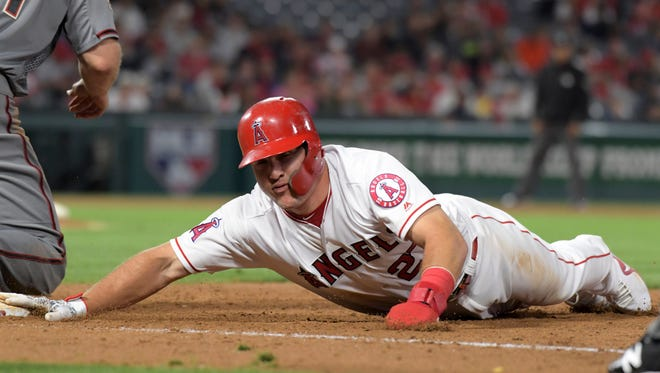 Jun 18, 2018; Anaheim, CA, USA; Los Angeles Angels center fielder Mike Trout (27) dives back to first base in the ninth inning against the Arizona Diamondbacks at Angel Stadium of Anaheim. The Diamondbacks defeated the Angels 7-4. Mandatory Credit: Kirby Lee-USA TODAY Sports