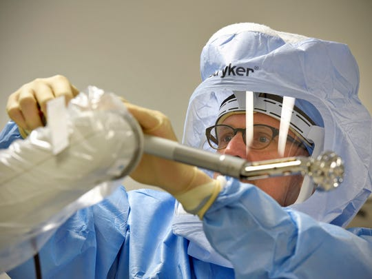 Dr. Joseph Nessler prepares a drill on a robotic arm