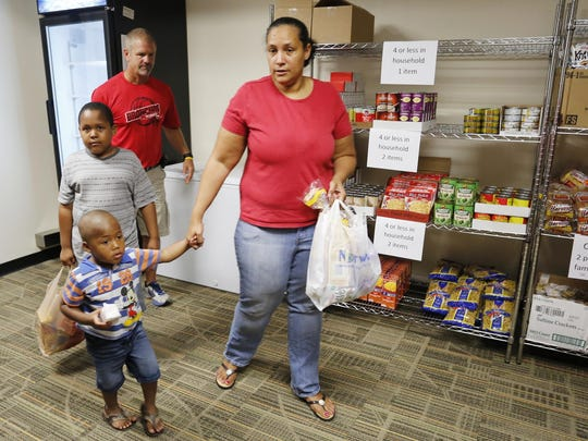 Joline Meyer and her sons Micheal Meyer, 3, and Jaikeam Jones, 7, leave the food pantry with two bags of groceries Thursday, September 10, 2015, inside Oakland Elementary School. Kirk Feaster, background, assisted Meyer and her sons. Oakland Elementary together with Food Finders Food Bank opened the food pantry to help feed students and their families who are struggling with food insecurity. Jaikeam, 7, is a second grade student at Oakland Elementary.