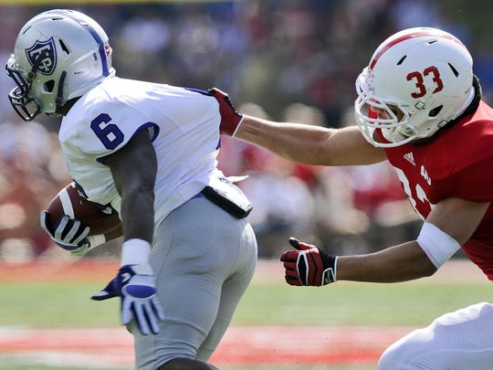 St. John's linebacker Andrew Rose (33) tries to get a handle on St. Thomas running back Aaron Terrell-Byrd during a game last season at Clemens Stadium. The Tommies defeated the Johnnies 43-21.