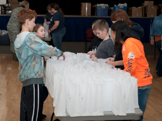 In 2014, children from Holloman Middle School help volunteers package cookies for the annual holiday cookie drive at Holloman Air Force Base, New Mexico on Dec. 8. More than 1,800 cookies were packaged last year for all the Airmen residing in the dorms on Holloman.