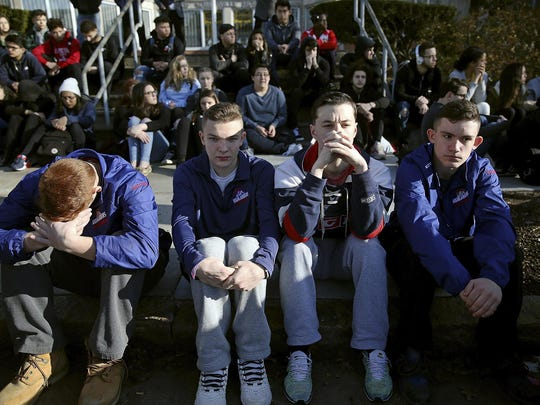 FILE - In this Feb. 28, 2018, file photo, Somerville High School students sit on the sidewalk on Highland Avenue during a student walkout at the school in Somerville, Mass. A large-scale, coordinated demonstration is planned for Wednesday, March 14, when organizers have called for a 17-minute school walkout nationwide to protest gun violence. (Craig F. Walker/The Boston Globe via AP, File)