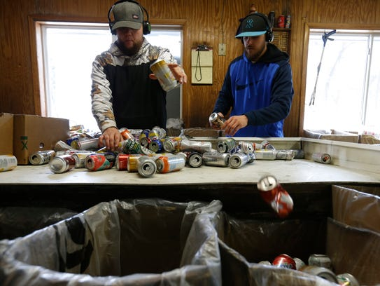 Josh Thompson, left, and Ben Allen sort through a bag of aluminum cans Thursday, March 16, 2017, the Kans R Us redemption center in Perry, Iowa. Thompson estimated they sort anywhere from 20, 000 to 40,000 cans a day, depending on how busy they are.