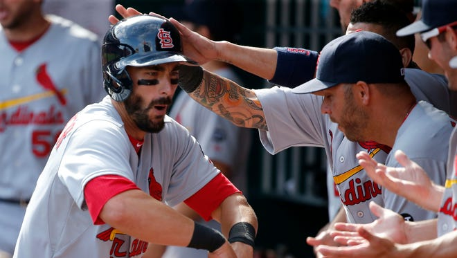 St. Louis Cardinals third baseman Matt Carpenter (13) is congratulated in the dugout after hitting a two-run home run in the 11 inning during the game, Sunday.