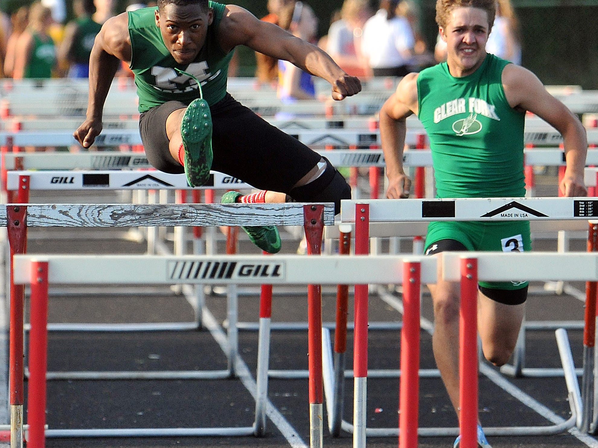 Madison's Frank Douglas clears a hurdle during the boys 100 Meter Hurdles at the OCC track meet at Madison High School Friday.