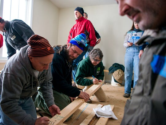 Volunteers work on the inside of an Asheville Area Habitat for Humanity house during the Before the Jam, Lend a Hand event, moved indoors due to snow.