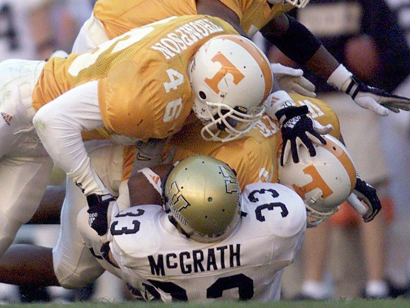 Vanderbilt running back Jared McGrath (33) is stopped cold by Tennessee defensive players Raynoch Thompson, Deon Grant and Fred White. No. 6 ranked Tennessee won 38-10 at Neyland Stadium Nov. 27, 1999.