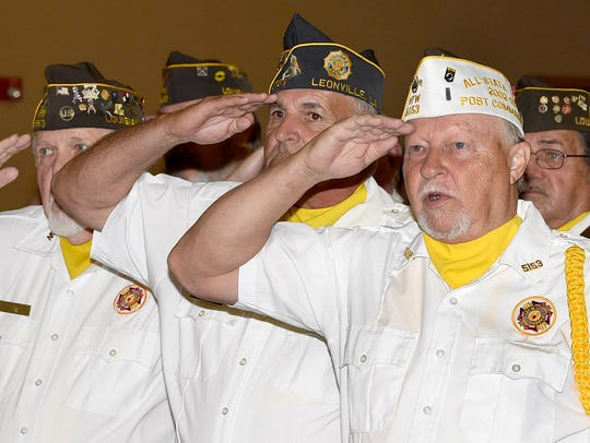 Veterans stand and salute at the playing of the National