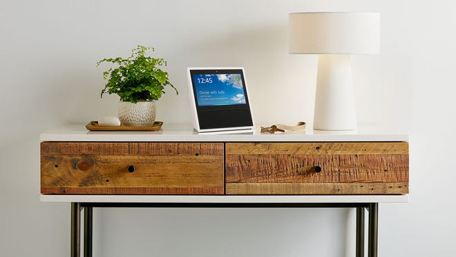 """FILE - This file photo provided by Amazon shows an Amazon Echo Show on display in a living room setting. With Echo Show, Amazon has given its voice-enabled Echo speaker a touch screen and video-calling capabilities as it competes with Google's efforts at bringing """"smarts"""" to the home. Amazon has been ramping up efforts to get more people to shop using the Alexa voice assistant on Echo speakers and other Amazon devices. (Amazon via AP, File)"""
