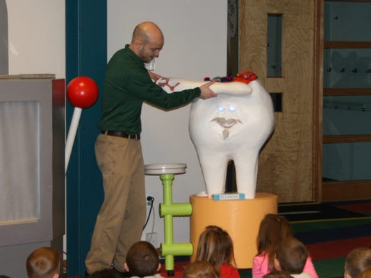 Sean Hermanns, an educator at Byrnes Health Education Center, demonstrates the proper way to brush teeth.