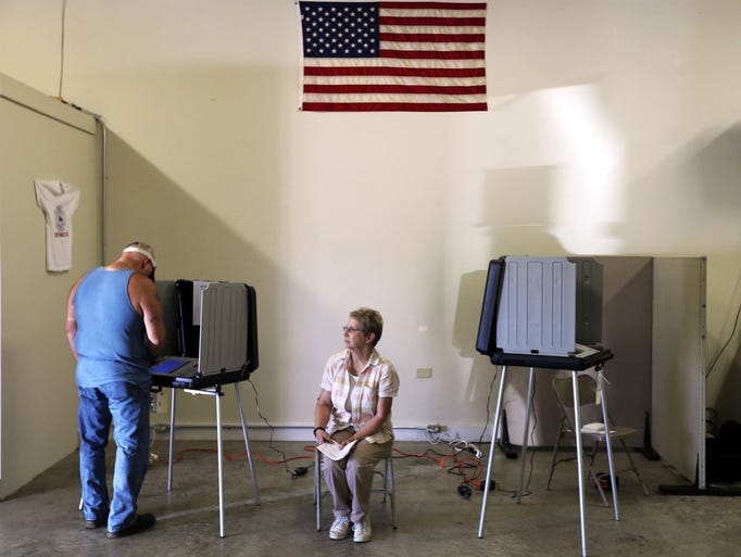 Poll worker Marie Steagall sits as David Short votes in the Republican primary elections at the Lascassas Volunteer Fire Department at Milton Tuesday, May 6, 2014.