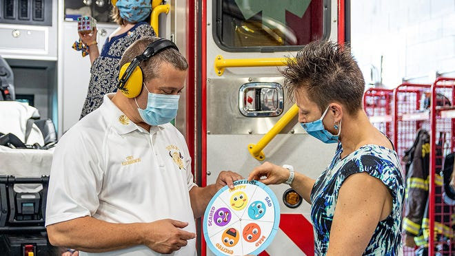 Misty Wisuri shows Dudley Fire Chief Dean Kochanowski the feelings wheel, an item in Sensory Sacks designed to calm children with autism.