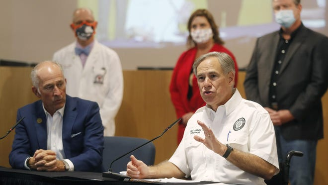 Texas Governor Greg Abbott talks to the media next to Lubbock Mayor Dan Pope during a press conference after attending a Lubbock Covid-19 Briefing with local officials in the Citizen's Tower Thursday, August 13.