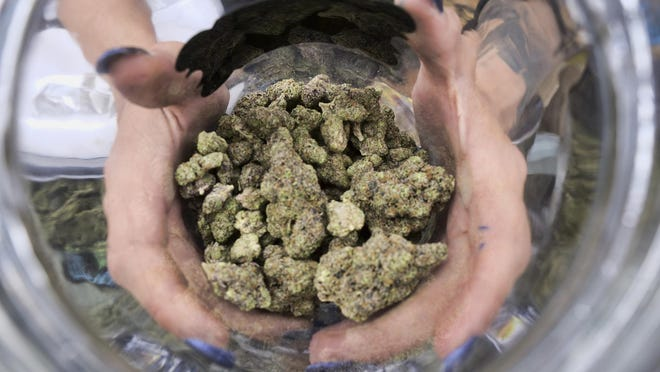 In this April 21, 2018, file photo a bud tender displays a jar of cannabis at the High Times 420 SoCal Cannabis Cup in San Bernardino, Calif.
