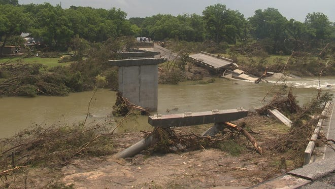 Floodwaters toppled the Fischer Store Road Bridge over the Blanco River west of Wemberley, Texas, on Saturday, May 23, 2015.