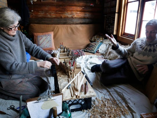 Victoria Jungwirth works on a miniature birchbark canoe on Feb. 9 as her husband John relaxes. They strive for authenticity in their work.