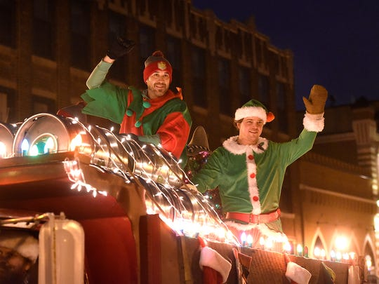 People on the Beaver Island Brewing float wave to the crowd during the 2015 Winter Nights and Lights parade in downtown St. Cloud.