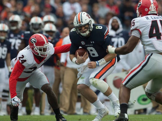 Georgia strong safety Dominick Sanders (24) tackles Auburn quarterback Jarrett Stidham (8) during the NCAA football game between Auburn and Georgia on Saturday, Nov. 11, 2017, in Auburn, Ala. 