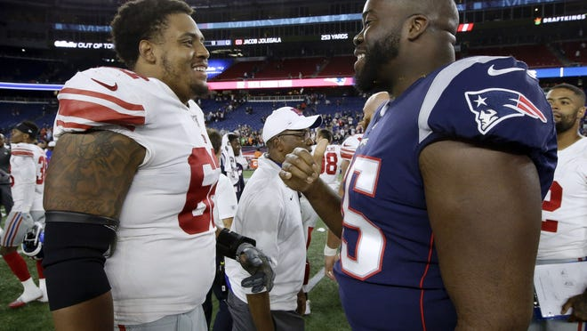 New England Patriots offensive tackle Yodny Cajuste (right) speaks with a New York Giants player at midfield after an NFL preseason football game on Aug. 29, 2019, in Foxborough. Could this be the season where you see Cajuste on the field for the Patritos?