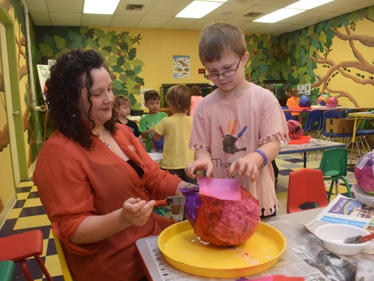 Kara Edwards (left), T.R.E.E. House Children's Museum director, helps Thomas Gilliand make a papier-mache birdhouse Wednesday during a summer camp held at the museum.