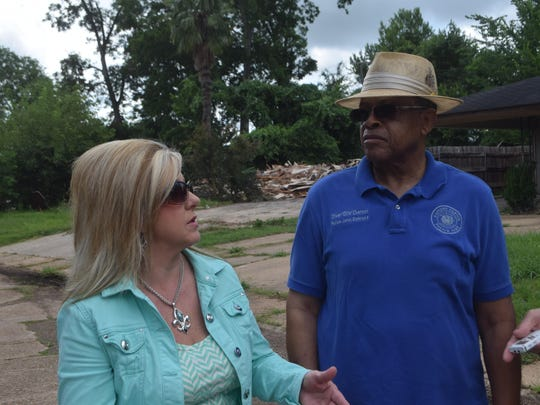 Melissa Becker of the Rapides Area Planning Commission talks with Rapides Parish Police Juror Ollie Overton on Friday as they walk around Greenway Park subdivision to check on the progress of a flood-mitigation project. Behind them is a house that was demolished this week as part of the project.