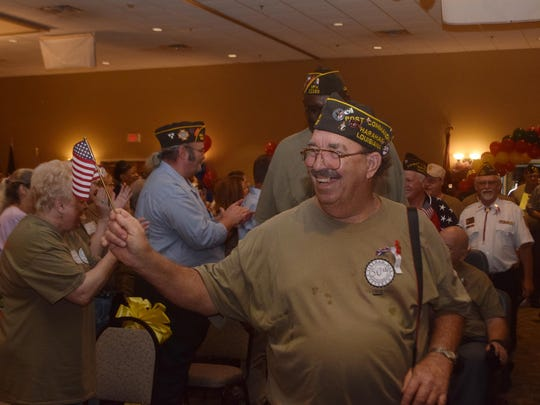 Larry Simmons, a U.S. Navy veteran who served in Vietnam from 1968-1972, smiles and waves an American flag as he and other Vietnam veterans parade into the meeting room at the Best Western Convention Center for the Veterans of Foreign Wars and Ladies Auxiliary's 84th annual State Convention Friday. Simmons is with VFW Post 3267 out of Harahan.