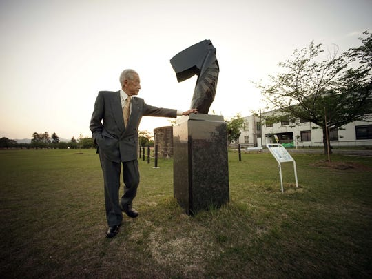 Yoshiomi Yanai, a survived kamikaze pilot, looks at a sculpture made by Masayuki Nagare, another survived kamikaze pilot as a war memorial and cenotaph for died kamikaze pilots during an exclusive interview with the Associated Press at Tsukuba Naval Air Group Base in Kasama, Ibaraki Prefecture, north of Tokyo.