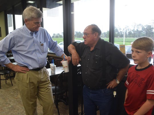 U.S. Sen. Bill Cassidy (left) talks with Terry Lee McGee (center) and his neighbor, Payton Bordelon, on Wednesday while Cassidy was working at the Y-Not-Stop convenience store on U.S. Highway 71 south of Alexandria. The National Association of Convenience Stores is hosting such events for members of Congress to understand the community experience of convenience stores and to give them a chance to talk to residents.