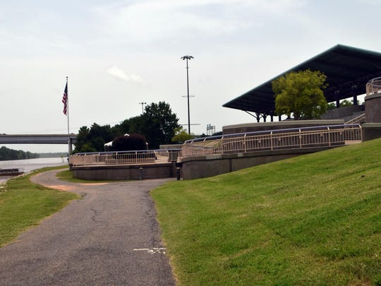This walking trail (foreground) winds along the Red River by the Alexandria Levee Park Amphitheatre (background). A group's development plan calls for a true boardwalk in that area.