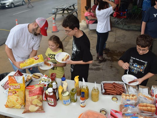 ANI Burnt Weenie Festival Erik Larson (far left) prepares hot dog plates for his children Alexis Larson and David Larson and Jack Blair (far right) gets some hot dogs at the annual Burnt Weenie Festival held Saturday at the Tamp & Grind Coffee House in dow