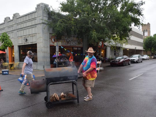 Eddy Lashney (right) moves a grill full of hot dogs to a carport across the street from the Tamp & Grind Coffee House on Fourth Street as Tamp & Grind owner Jeff Phillips carries the charcoal. Lashney and Phillips were hosting the annual Burnt Weenie Festival Saturday in downtown Alexandria.