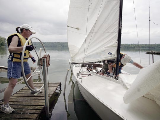 Sarah Russell and Chris Clarke bring in their sailboat at the Mansfield Sailing Club at the Clear Fork Reservoir.