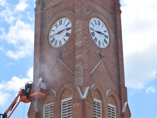 A worker uses a pressure washer to clean the brick of St. Frances Xavier Cathedral this month. Crews will be restoring the exterior for the next few months.
