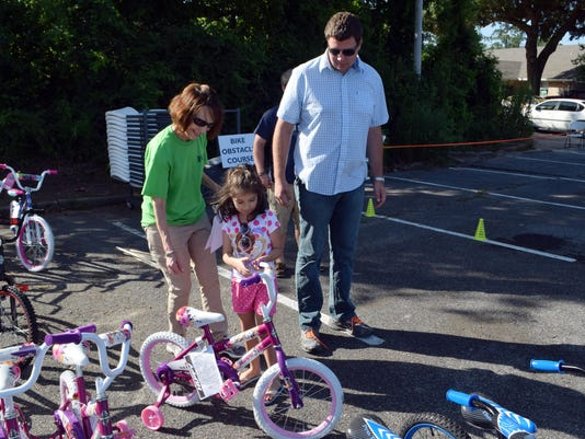 ANI Bike giveaway Lisa Allemand (left) of the Laborde Earles Law Firm, helps Abby Ledger (center) pick out her bike. With Abby is her brother Alex Snyder (right) who brought her to pick up her bike. Laborde Earles Law Firm gave away 100 bikes and helmets i