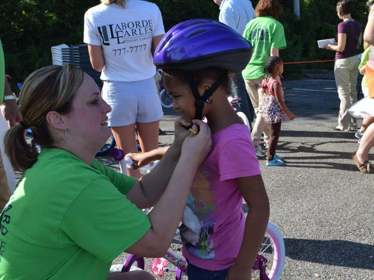 Erica Ducote (left) of the Laborde Earles Law Firm adjusts the bicycle helmet on Shalliea Moore. Laborde Earles Law Firm gave away 200 bikes and helmets in Alexandria and Lafayette on Friday.