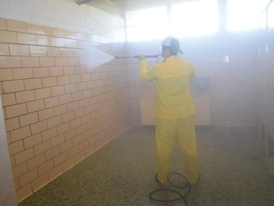 ANI Phoenix Magnet School Reldon Owens, a member of the Parent Teacher Organization at Phoenix Magnet School, pressure washes the boys' bathroom at the school. Members of the Parent Teacher Organization gathered at Phoenxi Saturday, July 25, 2015 to clean,