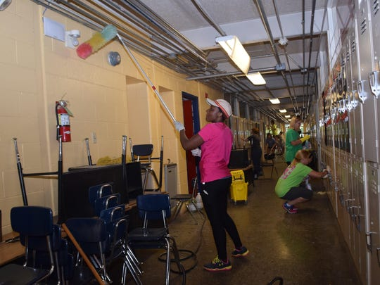 Stella Yonga, a member of the Parent Teacher Organization of Phoenix Magnet Elementary School, dusts pipes in a hall of the school. Members of the Parent Teacher Organization gathered at Phoenix on Saturday to clean, paint and landscape.