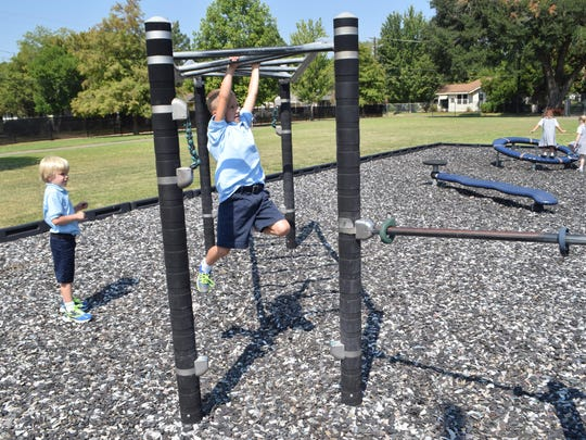 First-graders Jack Simpson (left) watches as Ethan Bridges climbs the monkey bars Friday at recess on the first day of school for Our Lady of Prompt Succor School.