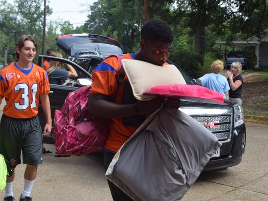 Louisiana College Wildcats football players Brandon Willams (front) and Doriel Yeager help students move items into Cottingham Hall on the Louisiana College campus Saturday.