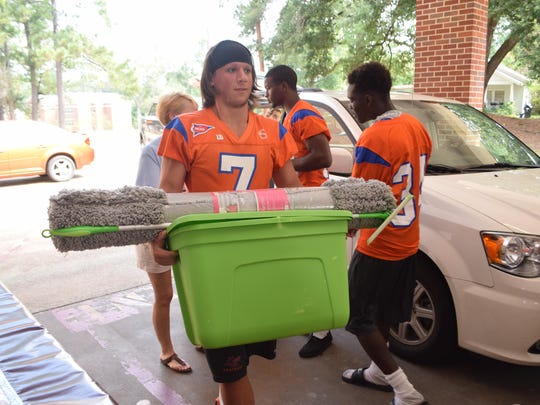 Louisiana College football player Easton Melancon and his teammates help students move items into Cottingham Hall on the Louisiana College campus Saturday.